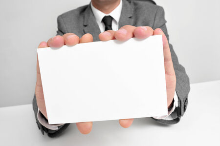 a man wearing a suit sitting in a desk holding a blank signboard with a copy-space photo