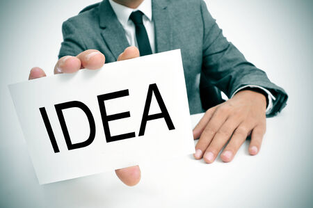 man wearing a suit sitting in a table showing a signboard with the word idea written in it photo