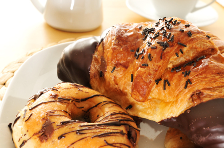 some pastries on a plate and a cup of coffee and a milk pot on a table photo