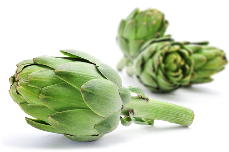 closeup of a pile of raw artichokes on a white background photo