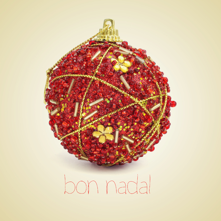 a red and golden christmas bauble and the text bon nadal, merry christmas written in catalan, on a beige background