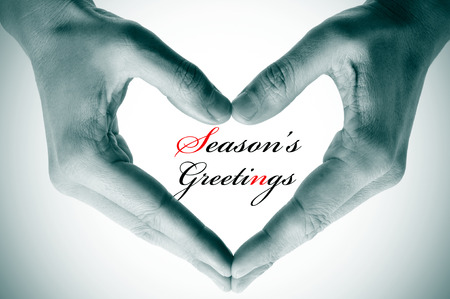 man hands forming a heart and the sentence seasons greetings photo
