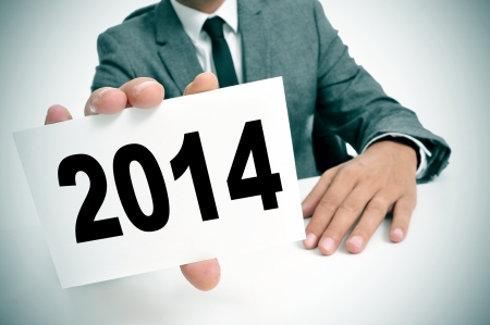 a man wearing a suit sitting in a desk showing a signboard with the number 2014, as the new year, written in it photo