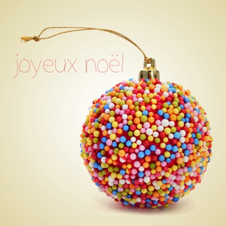 french text: a christmas ball coated with nonpareils of different colors and the sentence joyeux noel, merry christmas written in french, on a beige background