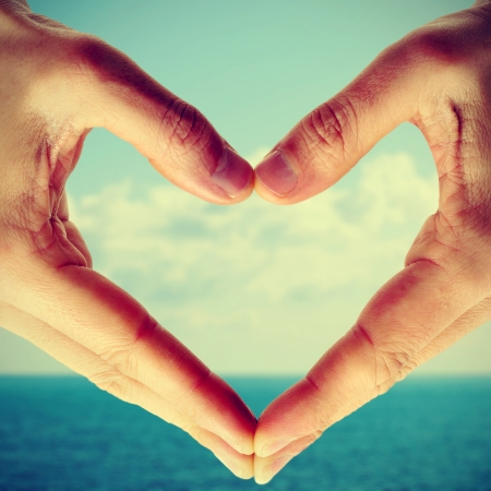 picture of man hands forming a heart with the sea and the sky in the background, with a retro effect photo