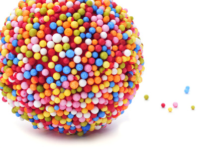 a ball coated with nonpareils of different colors on a white background photo