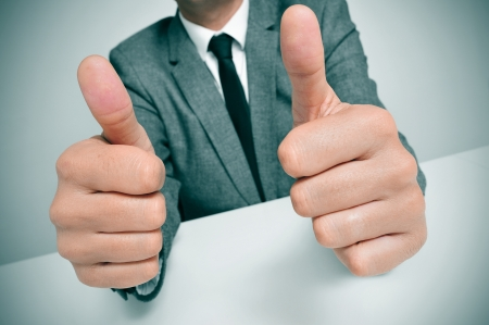 man wearing a suit sitting in a desk giving a thumbs up signal with both hands photo