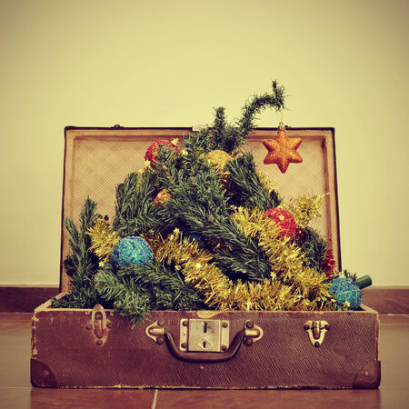 picture of a christmas tree coming out of an old suitcase, with a retro effect photo