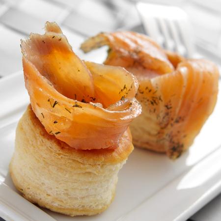 un plat avec quelques Volauvents remplis avec du saumon fumé, servi comme apéritif