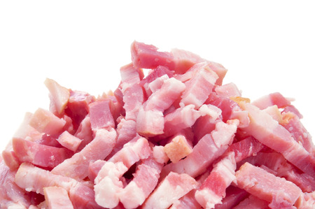 uncooked bacon: closeup of a pile of chopped raw bacon on a white background