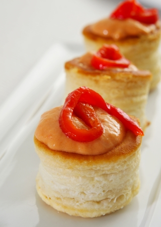 amuse: a plate with some volauvents filled with red pepper and cheese sauce, served as appetizer