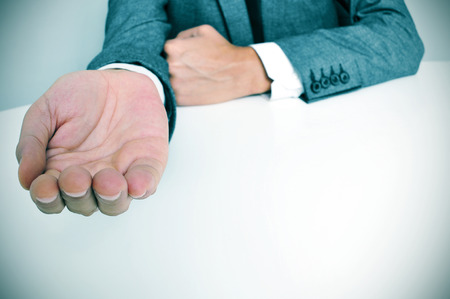 man wearing a suit sitting in a table with an outstretched hand photo