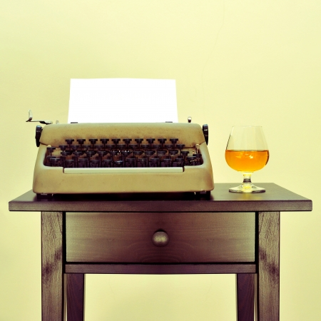 sleuth: an old typewriter with a blank page and a brandy snifter with liquor on a desk, with a retro effect Stock Photo