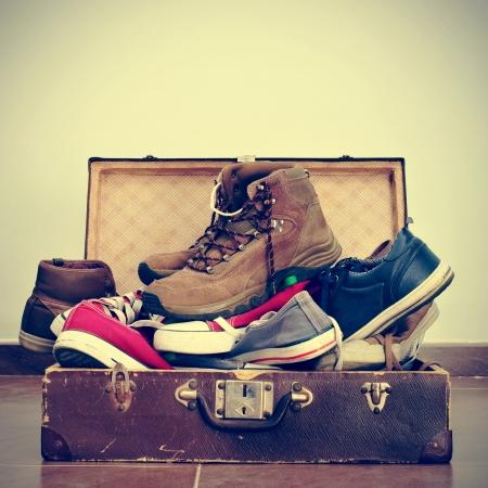 レトロな効果を持つ古い茶色スーツケースで靴の山