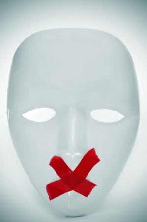 free thought: a white mask with its mouth shut with red tape, depicting the lack of freedom of speech Stock Photo