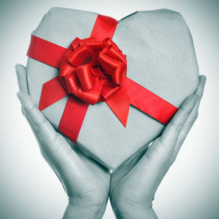 man hands holding a heart-shaped gift in black and white with a red ribbon photo
