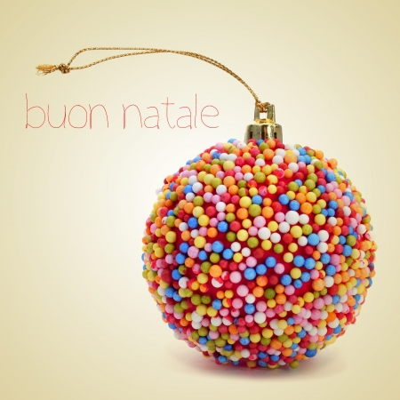 natale: a christmas ball coated with nonpareils of different colors and the sentence buon natale, merry christmas written in italian, on a beige background