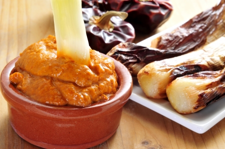 calsotada: closeup of a plate with barbecued calcots, sweet onions, and a bowl with romesco sauce, typical of Catalonia, Spain