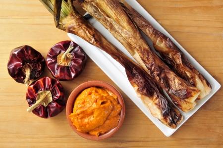 Primer plano de una placa con calcots asadas, cebollas dulces, y un plato con salsa romesco, típico de Cataluña, España