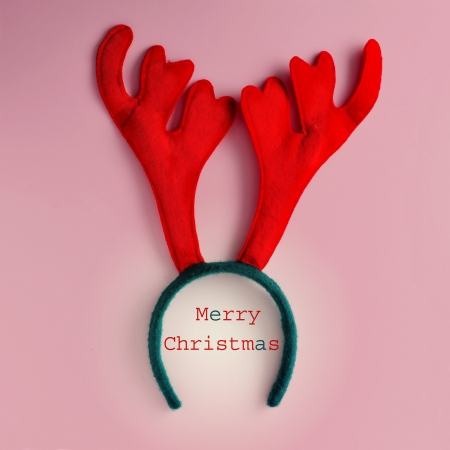 colorful reindeer antlers headband and sentence merry christmas in a pink background photo