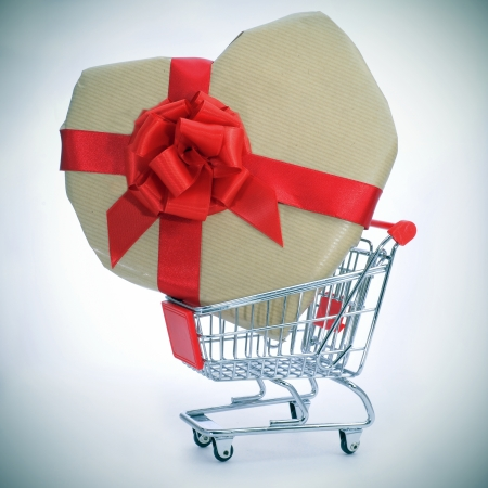 a heart-shaped gift with a red ribbon in a shopping cart photo