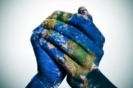 diversidad cultural: un mapa del mundo en las manos del hombre que forma un globo (Mapa de la tierra proporcionada por la NASA) Foto de archivo