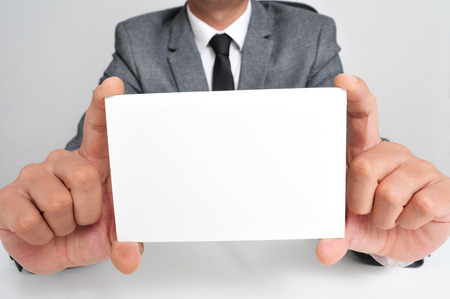 headman: a man wearing a suit sitting in a desk holding a blank signboard with a copy-space