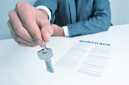 renter: a man wearing a suit sitting in a desk with a mortgage contract giving a key ring to the observer Stock Photo