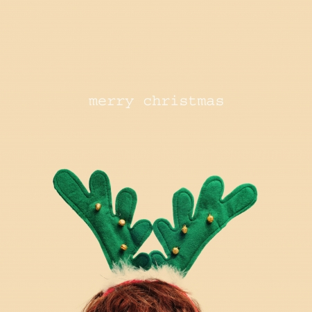 christmas costume: someone wearing a reindeer antlers headband and the sentence merry christmas in a beige background Stock Photo