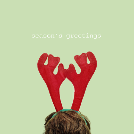 christmas costume: someone wearing a reindeer antlers headband and the sentence seasons greetings in a green  background