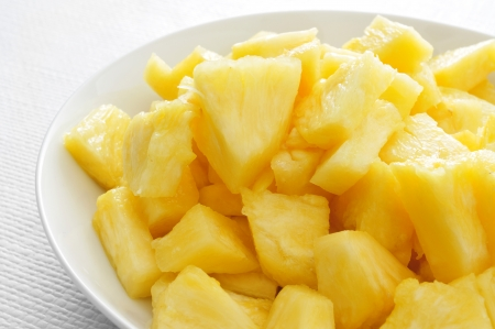 diced: closeup of a bowl with diced pineapple served as dessert on a set table Stock Photo