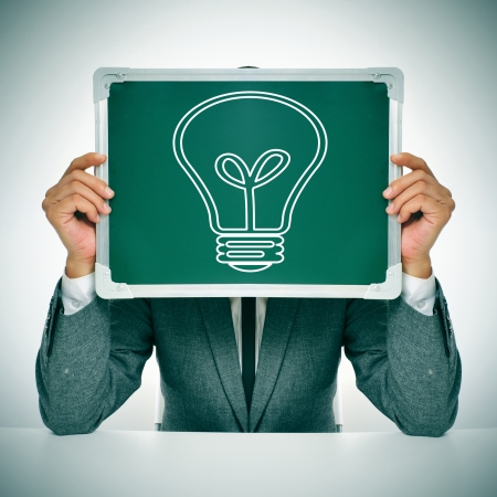 headman: man wearing a suit sitting in a table holding a chalkboard in front of his face with a light bulb drawn in it