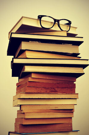 a pile of books and eyeglasses symbolizing the concept of reading habit or studying photo