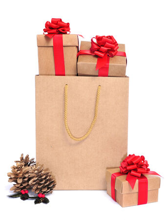 pinecones: a pile of gifts with a red ribbon in a shopping bag and some golden pinecones on a white background  Stock Photo