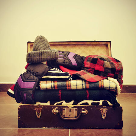 a pile of warming clothes, such as gloves, caps or blankets, in an old suitcase, with a retro effect photo