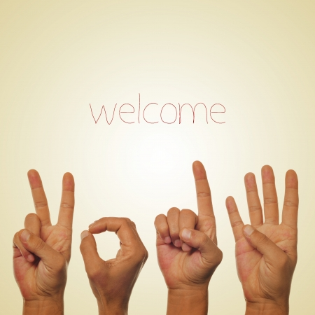 word welcome and hands forming number 2014 on a beige background, with a retro effect photo