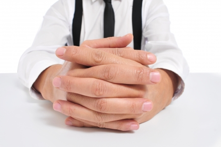 willing: businessman sitting in a table with clasped hands