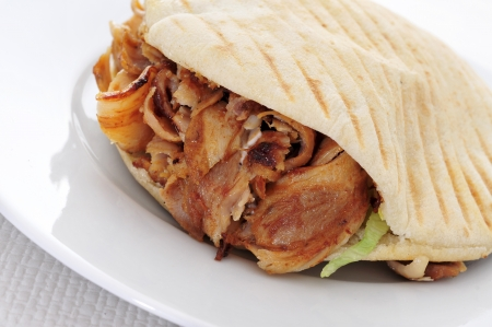 a doner kebab in a plate on a set table photo