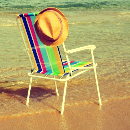 picture of a colored deckchair and a straw hat on the beach, with a retro effect photo