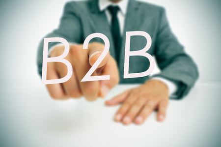 man wearing a suit sitting in a table pointing to the word B2B, business-to-business, written in the foreground photo