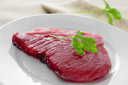 ahi: closeup of a raw tuna steak in a plate Stock Photo