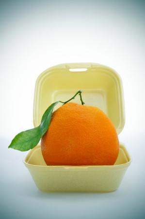 Hábitos saludables: una naranja apetitoso en un envase de alimento de la espuma, como la comida rápida, esto es fruto rápido, o que simboliza la sustitución de la comida rápida de comida sana