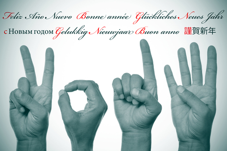 anno: sentence happy new year written in different languages, such as spanish, french, german, russian, dutch, italian and japanese, and hands forming number 2014