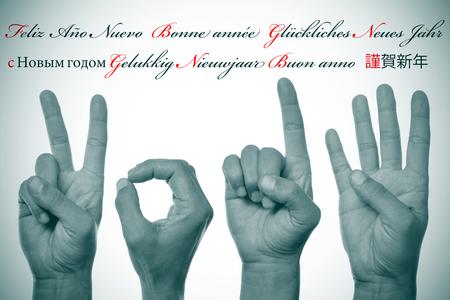 oracion: sentenciar feliz a�o nuevo escrito en diferentes idiomas, como el espa�ol, franc�s, alem�n, ruso, holand�s, italiano y japon�s, y las manos formando n�mero 2014