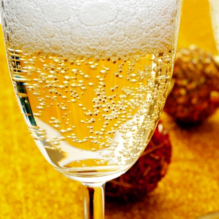 some glasses with champagne and some christmas balls in the background