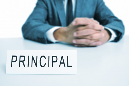 a man wearing a suit sitting in a desk with a signboard in front of him with the word principal written in it photo