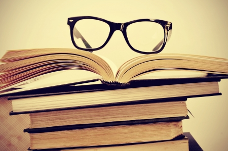 picture of a pile of books and eyeglasses, with a retro effect photo