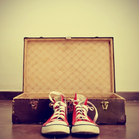 footgear: a pair of red sneakers in front of an open old brown suitcase with a retro effect Stock Photo