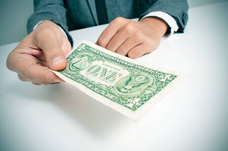 a man wearing a suit sitting in a desk offering a one US dollar bill photo