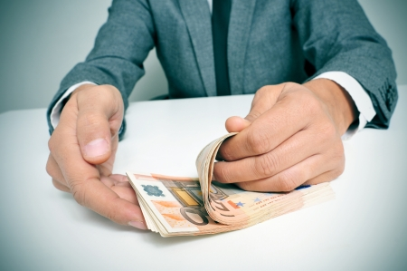 bank notes: a man wearing a suit sitting in a desk counting euro bills Stock Photo